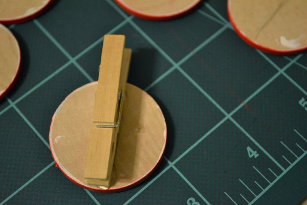 Glue clothespins to back of wooden nickels