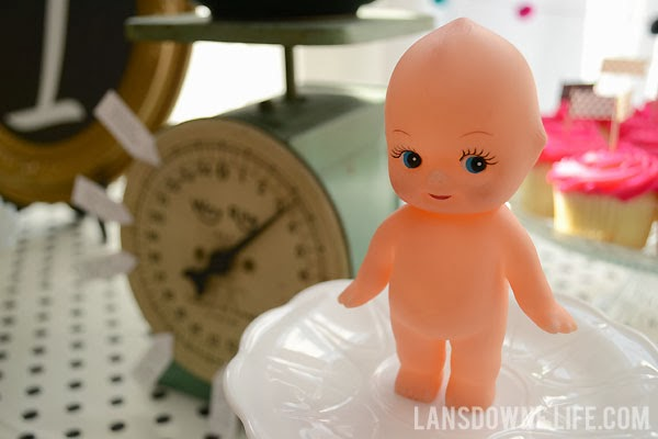Vintage kewpie doll as a first birthday party decoration